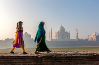 Women walking Mehtab Bagh, Moon Garden across from Taj Mahal in morning mist. Agra. India.