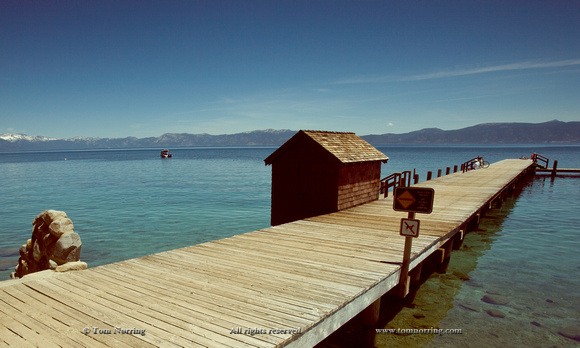 Lonely boathouse and resting bikers at Lake Tahoe, California, USA