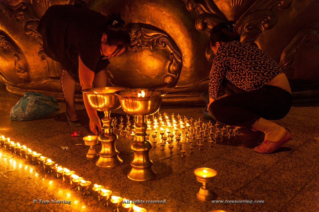 Women lighting prayer candles at Gandan Monastery, Mongolia's largest functioning monastery,Mongolia,Ulaanbaator
