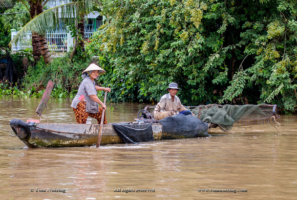 Husband and wife setting nets for daily catch in the River,  Mekong River Delta. Vietnam, Indochina, South East Asia. Orient. Asia.